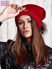 Czerwona czapka z futrzanym pomponem i przypinką