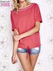 Koralowy t-shirt z różowymi pomponikami przy dekolcie