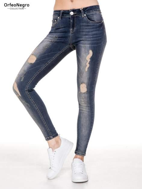 Ciemnoniebieskie rozjaśniane spodnie jeansowe rurki z przetarciami