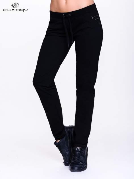 Czarne spodnie dresowe z dżetami przy kieszeniach