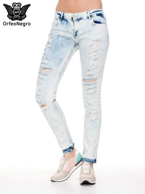 Jasnoniebieskie spodnie jeansowe rurki z przetarciami i poszarpaną na dole nogawką