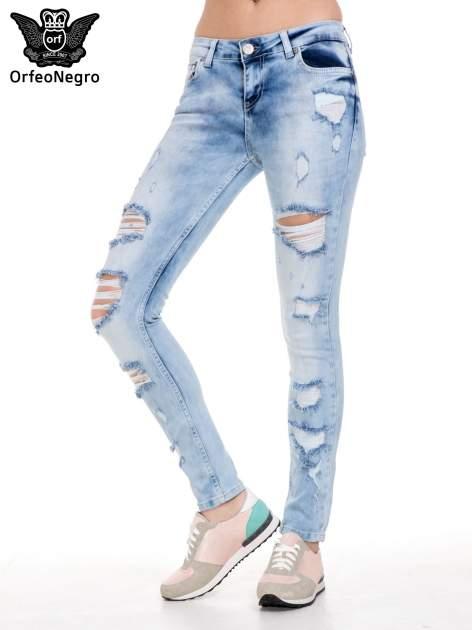 Jasnoniebieskie spodnie jeansowe rurki z rozdarciami i przetarciami