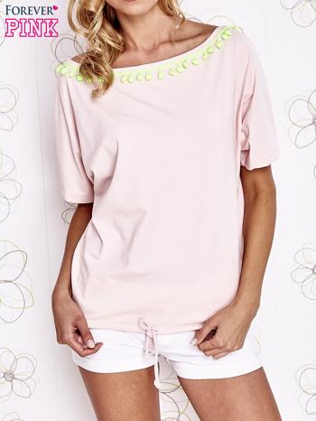Jasnoróżowy t-shirt z limonkowymi pomponikami przy dekolcie