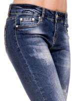 Ciemnoniebieskie spodnie skinny jeans z dziurami i zamkami
