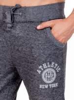 Czarne melanżowe spodnie męskie z kieszeniami i aplikacją