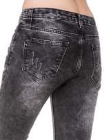 Czarne spodnie jeansowe rurki z dziurami przetarciami