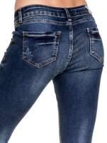Granatowe spodnie skinny jeans z przecieraną nogawką z przodu