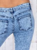 Niebieskie jeansowe spodnie rurki marmurkowe z dziurami