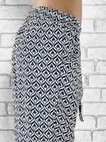 Niebieskie zwiewne spodnie alladynki we wzór geometryczny