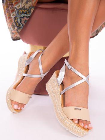 Beżowe sandały na podwyższeniu z ozdobnym srebrnym paskiem zapinanym na kostkach