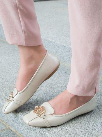 Beżowo-perłowe tłoczone baleriny Monnari z ozdobną złotą przypinką na przodzie buta