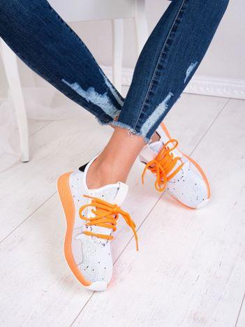 Białe dzianinowe buty sportowe z neopomarańczowymi elementami