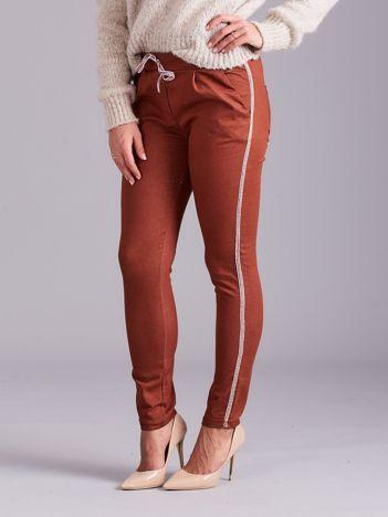Brązowe spodnie z troczkami i lampasami