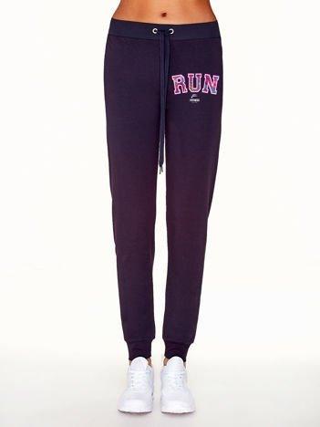 Ciemnofioletowe spodnie dresowe ze sportowym nadrukiem