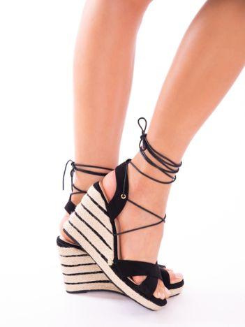 Czarne sandały na koturnach z ozdobnymi paskami, wiązane wokół kostek