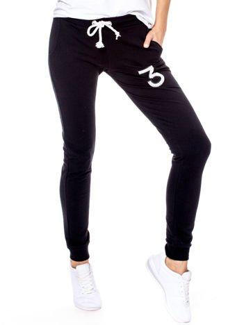 Czarne spodnie dresowe z białymi troczkami i błyszczącą cyfrą