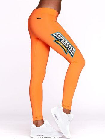 Fluo pomarańczowe legginsy sportowe z nadrukiem SUPERSTAR
