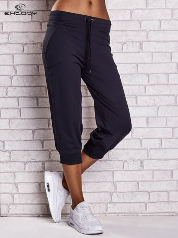 Granatowe spodnie damskie capri z kieszonką i haftem PLUS SIZE