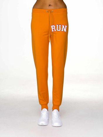 Jasnopomarańczowe spodnie dresowe z napisem RUN
