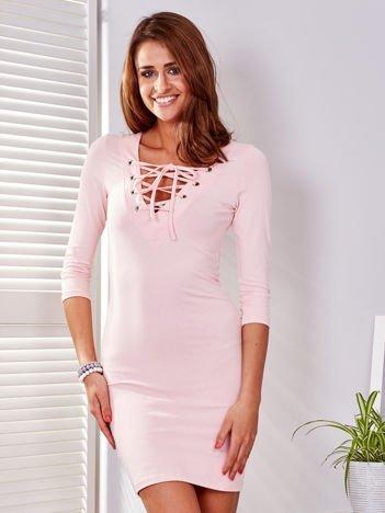 Jasnoróżowa dopasowana sukienka ze sznurowanym dekoltem
