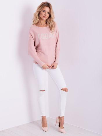 Jasnoróżowy sweter oversize z błyszczącym napisem