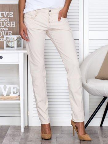 Kremowe materiałowe spodnie regular na guziki