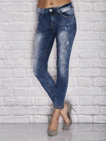 Niebieskie dekatyzowane spodnie jeansowe z przetarciami