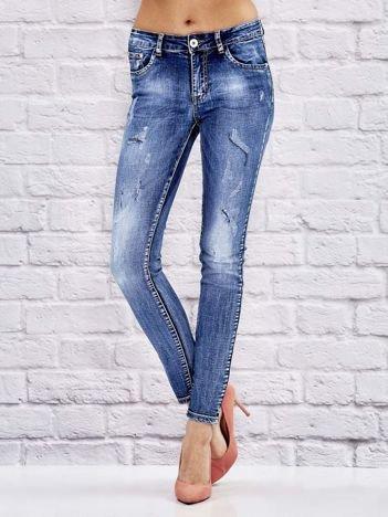 Niebieskie dekatyzowane spodnie jeansowe z przetarciami i szwami