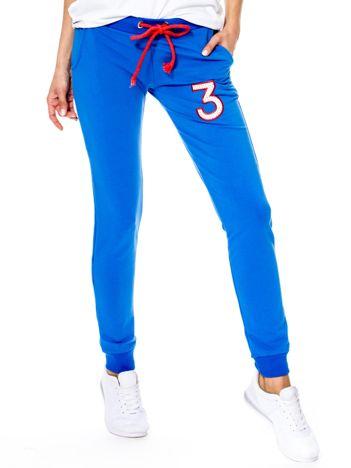 Niebieskie spodnie dresowe z troczkami i błyszczącą cyfrą