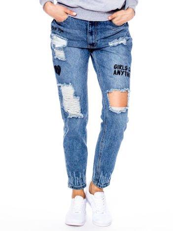 Niebieskie spodnie mom jeans z dziurami i nadrukami