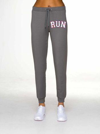Oliwkowe spodnie dresowe z napisem RUN