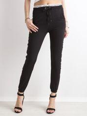 Czarne damskie spodnie dresowe z lampasami