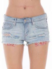 Niebieskie jeansowe szorty z wystającymi kieszeniami
