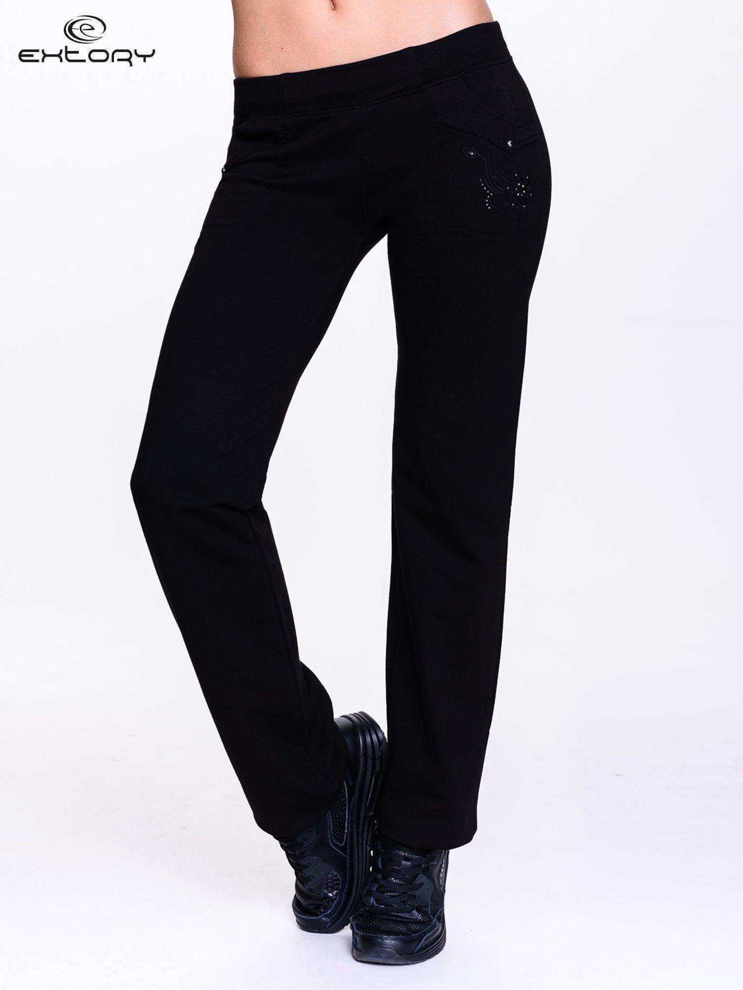 Czarne spodnie dresowe z kwiatem z dżetami                                  zdj.                                  1