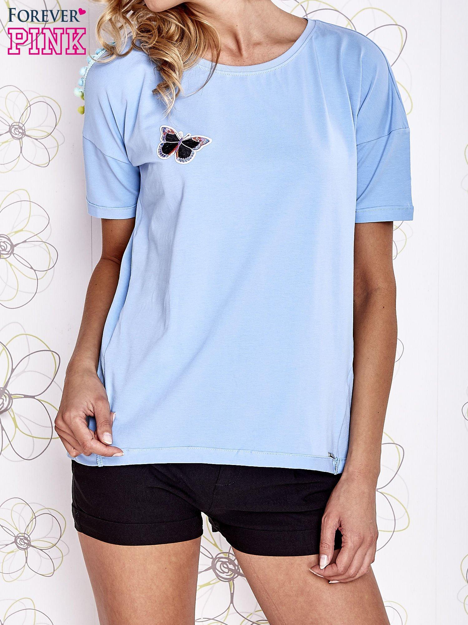 Jasnoniebieski t-shirt z naszywką motyla i pomponami                                  zdj.                                  1