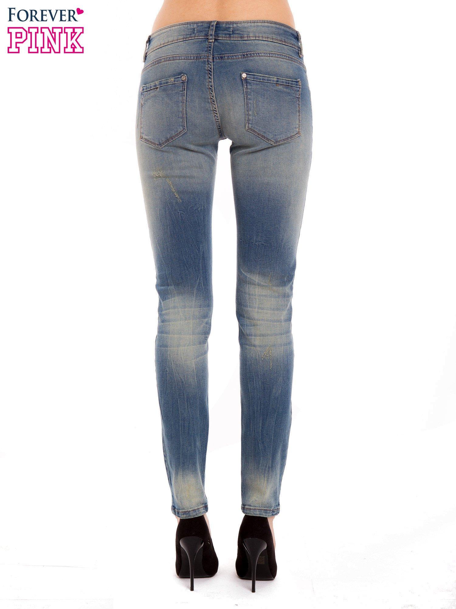 Jasnoniebieskie jeansy rurki z dziurą na kolanie                                  zdj.                                  4