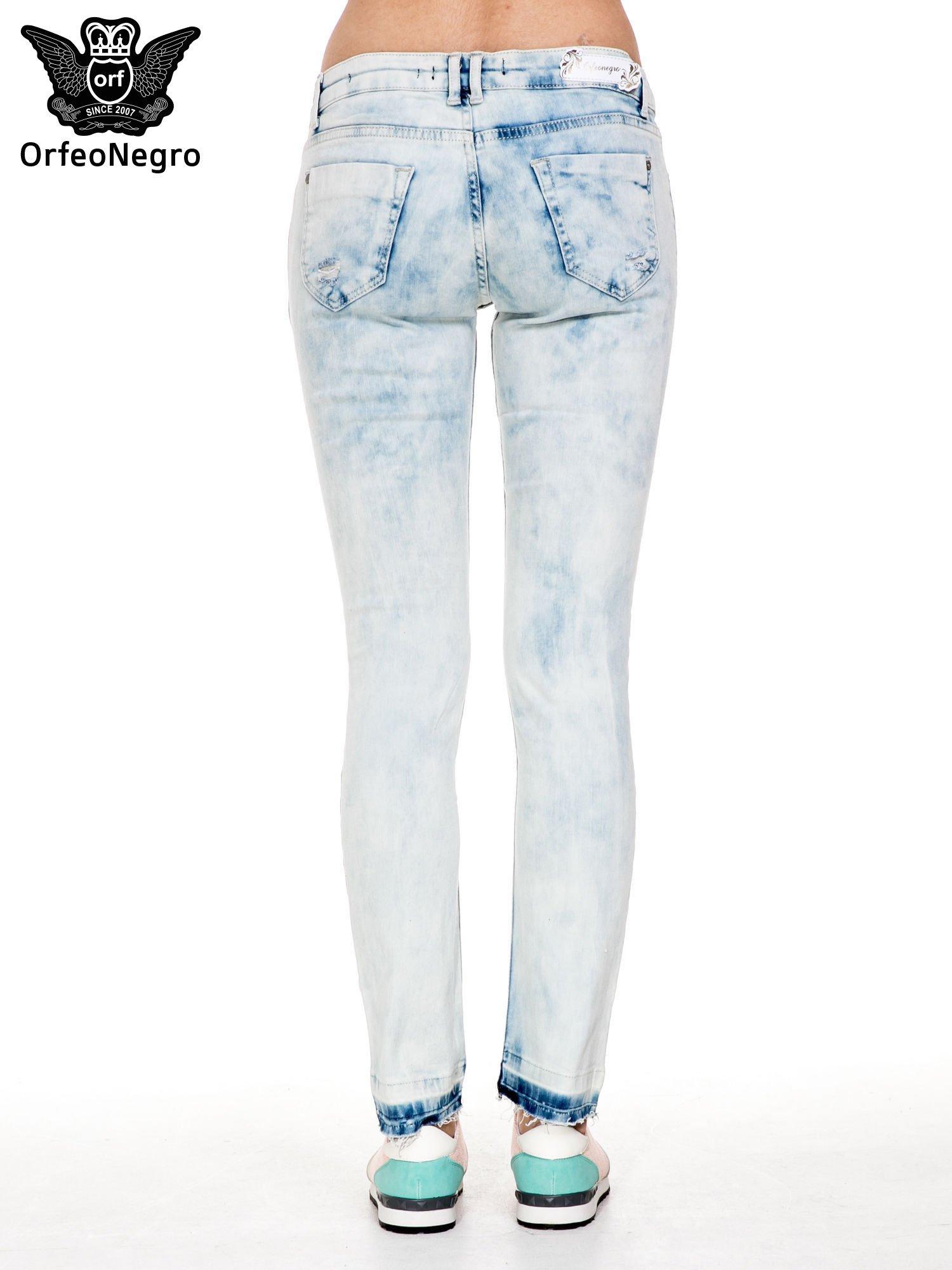 Jasnoniebieskie spodnie jeansowe rurki z przetarciami i poszarpaną na dole nogawką                                  zdj.                                  4
