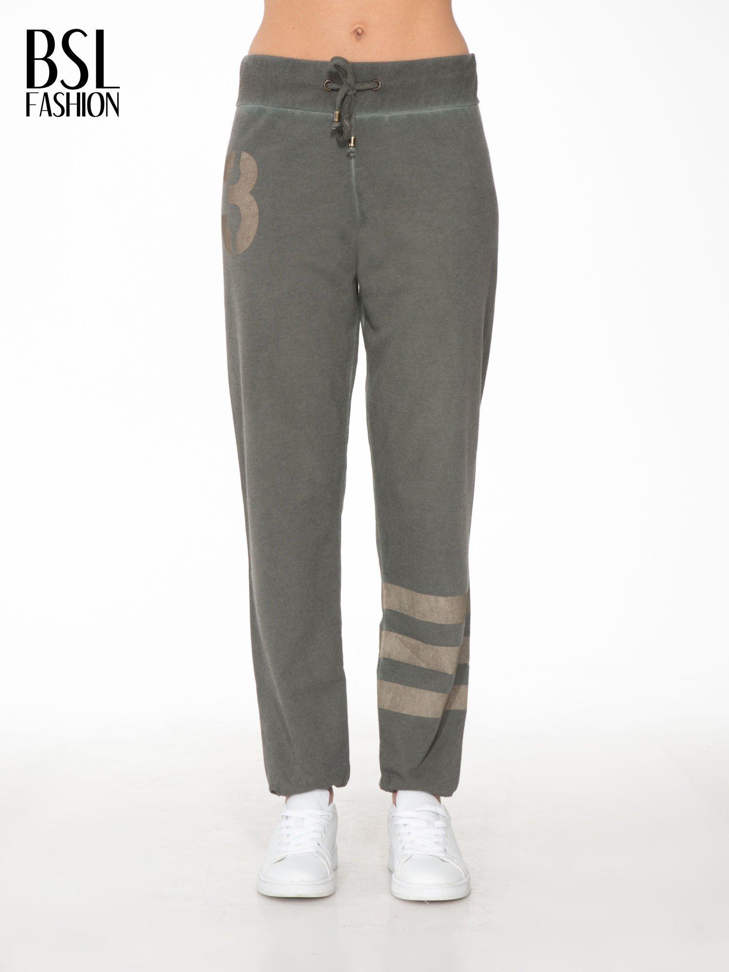 Khaki dresowe spodnie damskie z numerkiem i paskami na nogawkach                                  zdj.                                  1