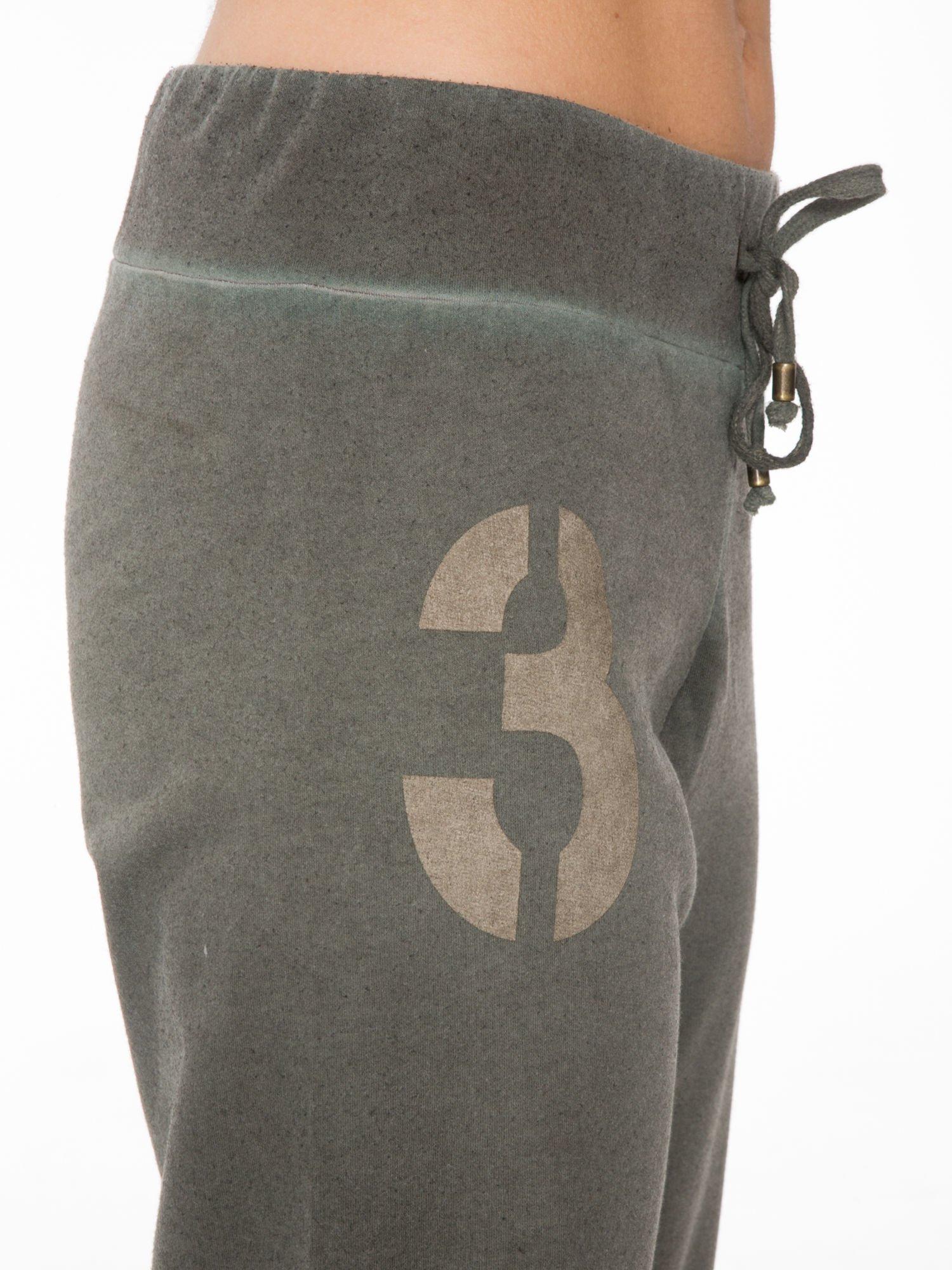 Khaki dresowe spodnie damskie z numerkiem i paskami na nogawkach                                  zdj.                                  6