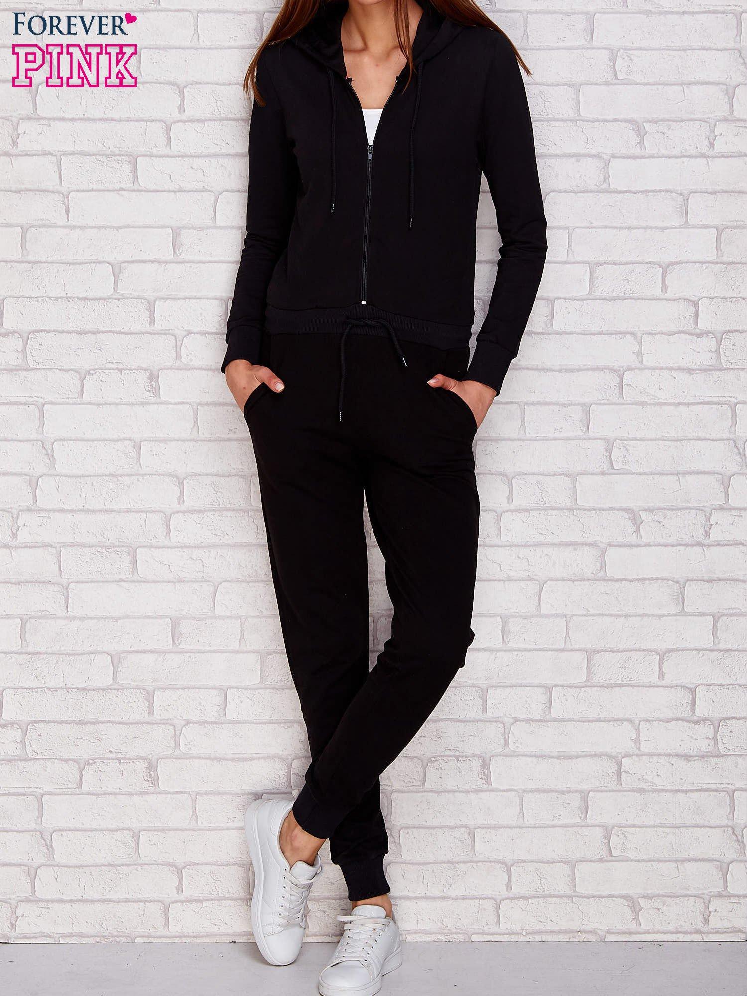 1b56dbfb0ec7d0 Kombinezon dresowy z kapturem czarny - Spodnie Kombinezony - sklep ...