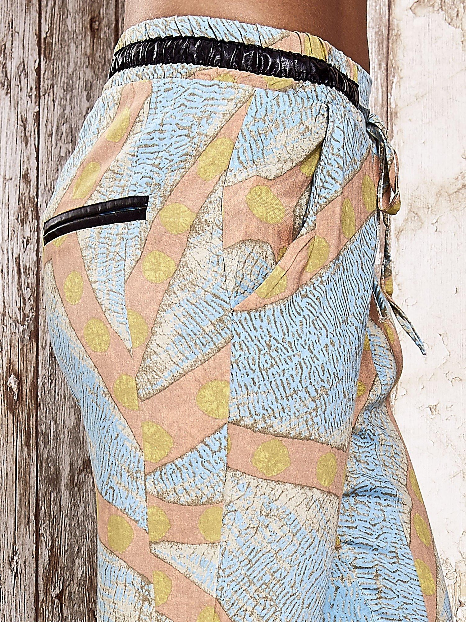 Niebieskie lejące spodnie z artystycznym nadrukiem                                  zdj.                                  5