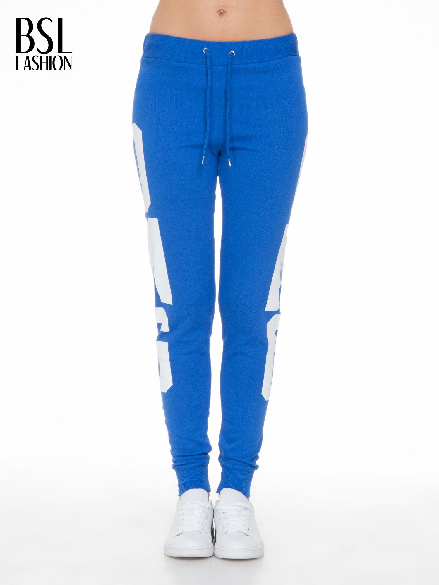 Niebieskie spodnie dresowe z nadrukiem OMG z boku nogawek                                  zdj.                                  1