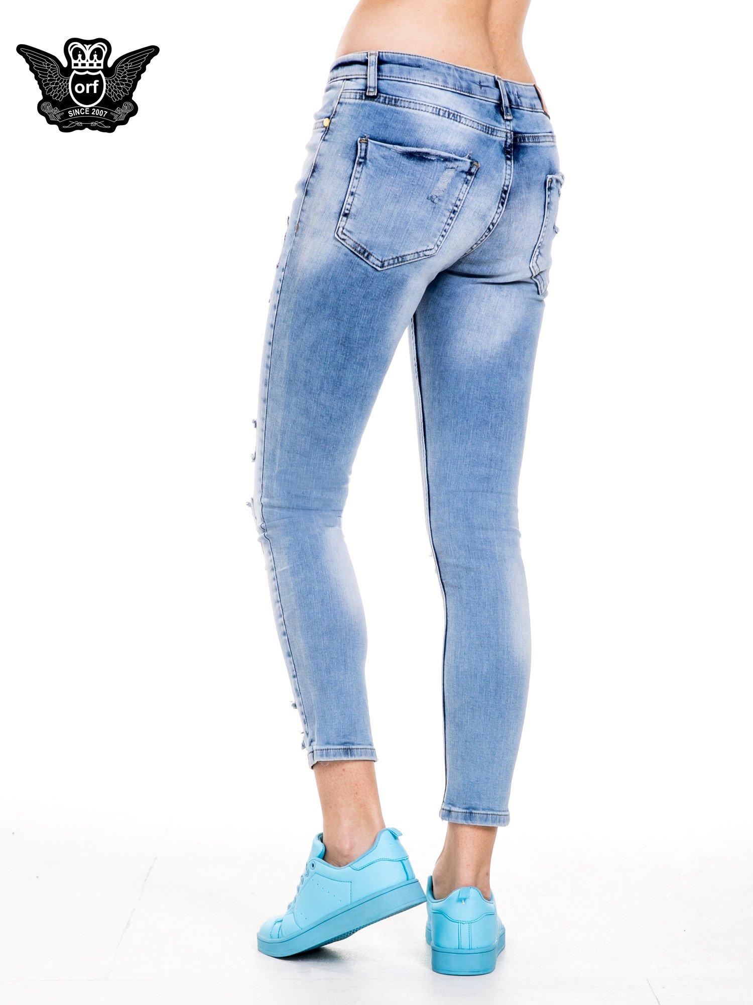 Niebieskie spodnie jeansowe z dziurami i rozdarciami                                  zdj.                                  2