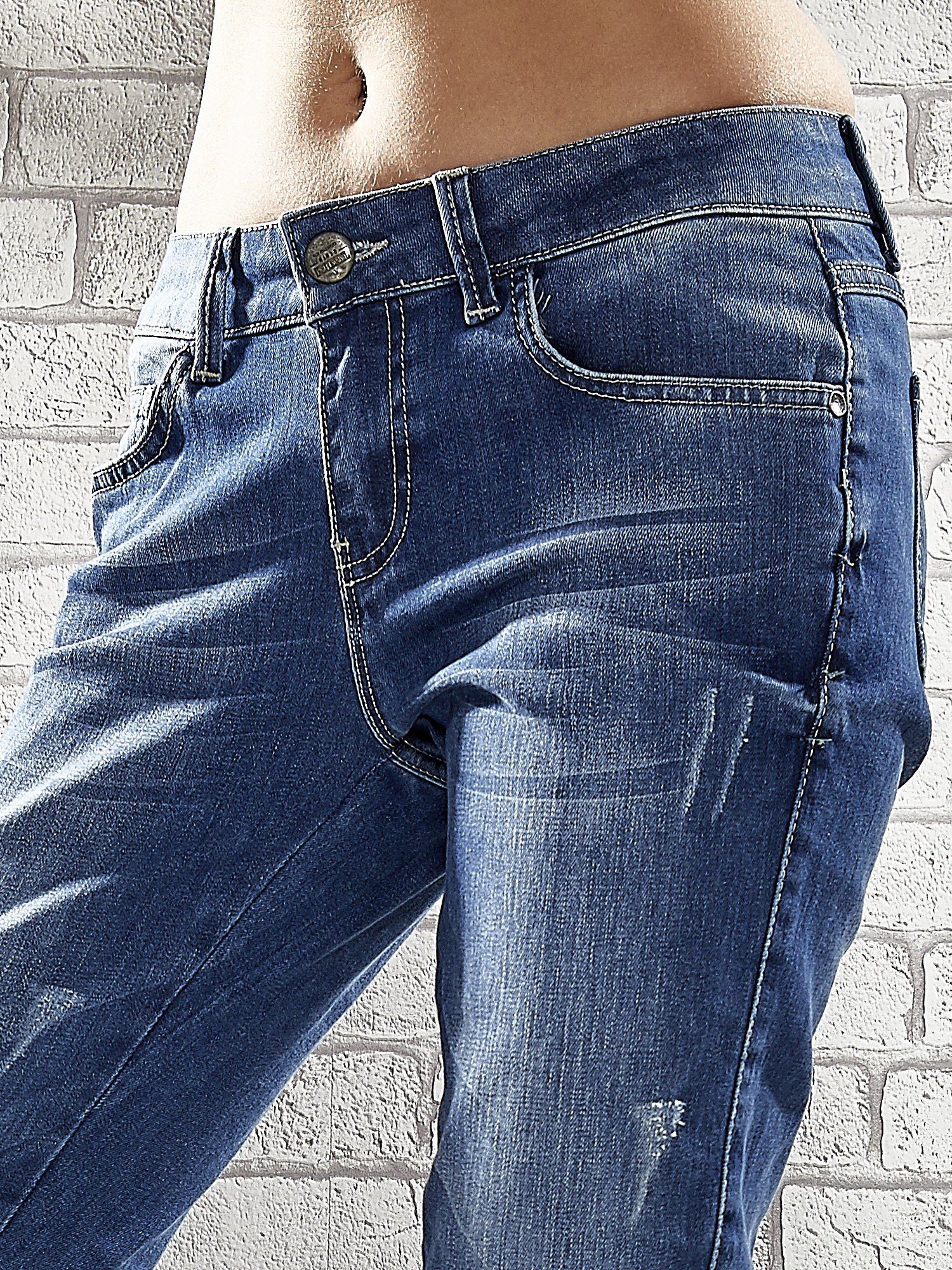 Niebieskie spodnie skinny jeans z postrzępioną nogawką na dole                                  zdj.                                  4