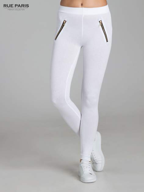 Białe legginsy ze złotymi zamkami