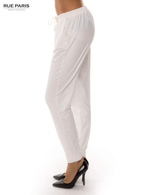 Białe spodnie dresowe ze zwężanymi nogawkami z efektem połysku                                  zdj.                                  3