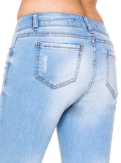 Błękitne spodnie jeansowe rurki z rozdarciam na kolanach                                  zdj.                                  8