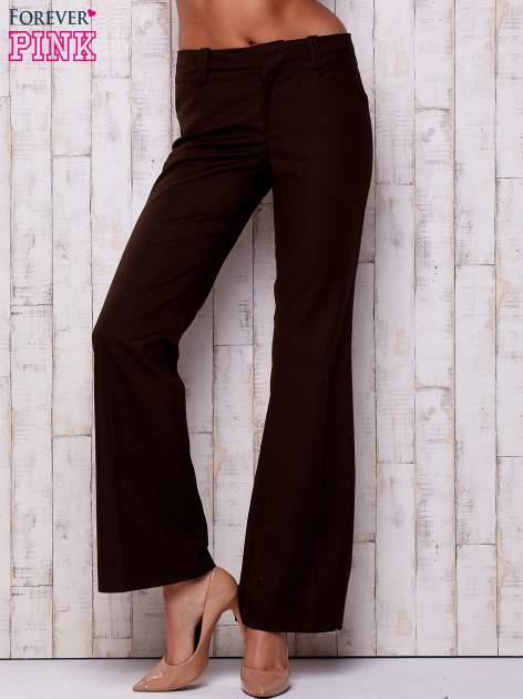 Brązowe materiałowe rozszerzane spodnie                                  zdj.                                  1