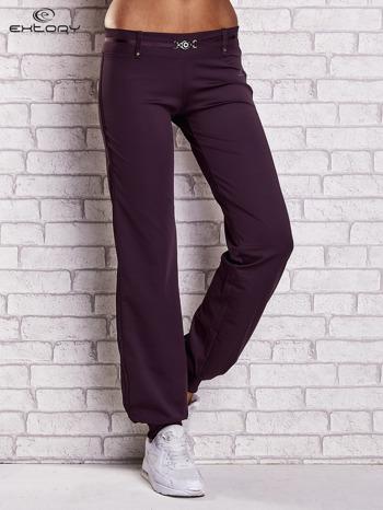 Ciemnofioletowe spodnie dresowe z ozdobnym paskiem                                  zdj.                                  1