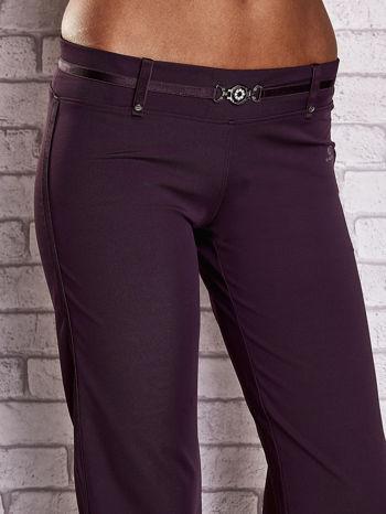 Ciemnofioletowe spodnie dresowe z ozdobnym paskiem                                  zdj.                                  4